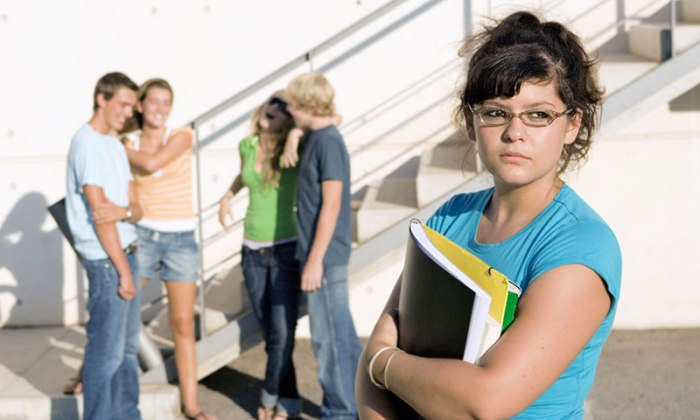 outcast sad girl at university with group of friends behind